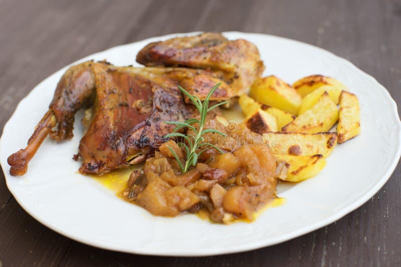 Las aves de Guinea asadas o cocidas sirvieron con las patatas cocidas y la cebolla dulce con las manzanas y las pasas fotos de archivo libres de regalías