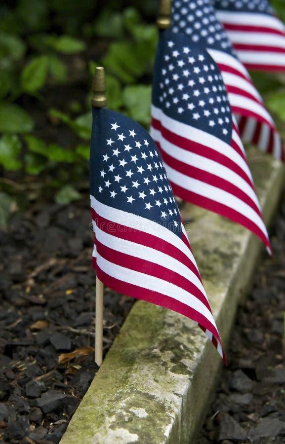 Las banderas americanas alinean la trayectoria del jardín imagenes de archivo