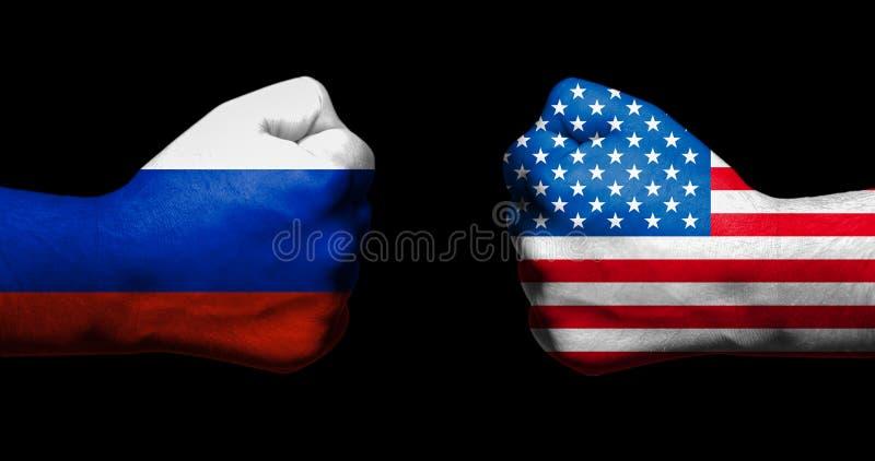 Las banderas de los E.E.U.U. y de Rusia pintados en dos apretaron los puños que se hacían frente en fondo negro/la relación tensa imagen de archivo libre de regalías