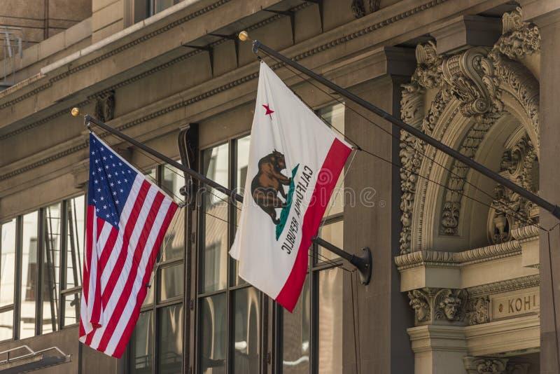 Las banderas de los Estados Unidos y de la California en un edificio en el distrito financiero de San Francisco, California, los  fotos de archivo