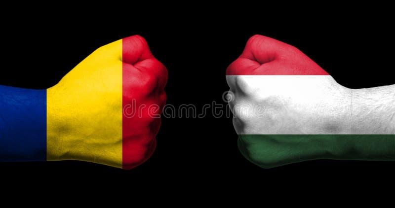 Las banderas de Rumania y de Hungría pintadas en dos apretaron los puños que se hacían frente en concepto negro del fondo/de las  imagen de archivo libre de regalías