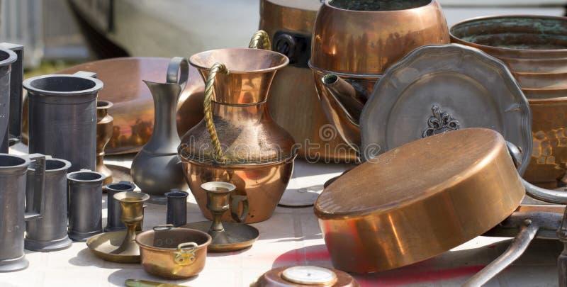 Las baratijas del cobre y de la lata se oponen en el mercado de pulgas fotografía de archivo