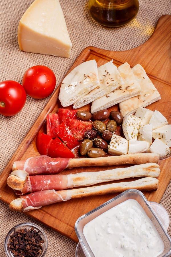 Las barras de pan con el prosciutto curaron la carne en un tablero de madera imagen de archivo libre de regalías
