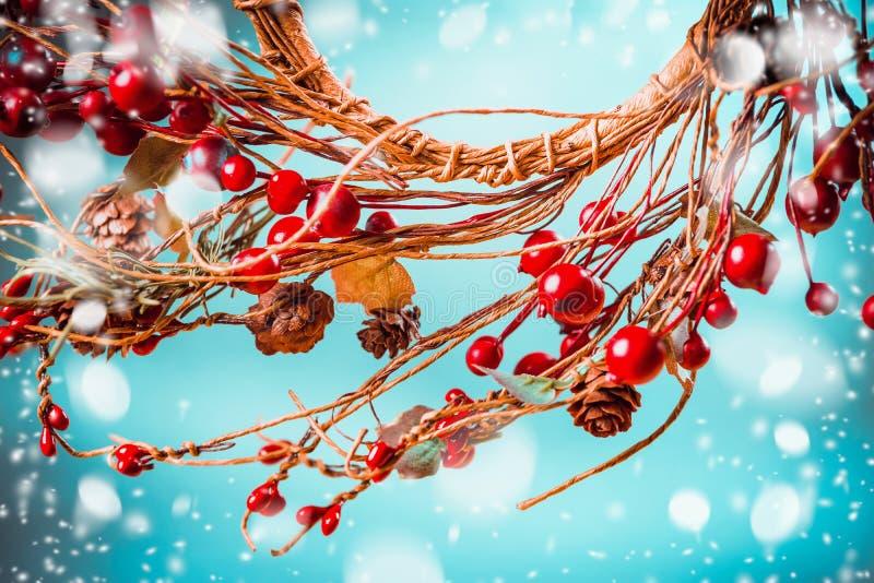 Las bayas rojas de la Navidad enrruellan en fondo azul con nieve fotos de archivo libres de regalías