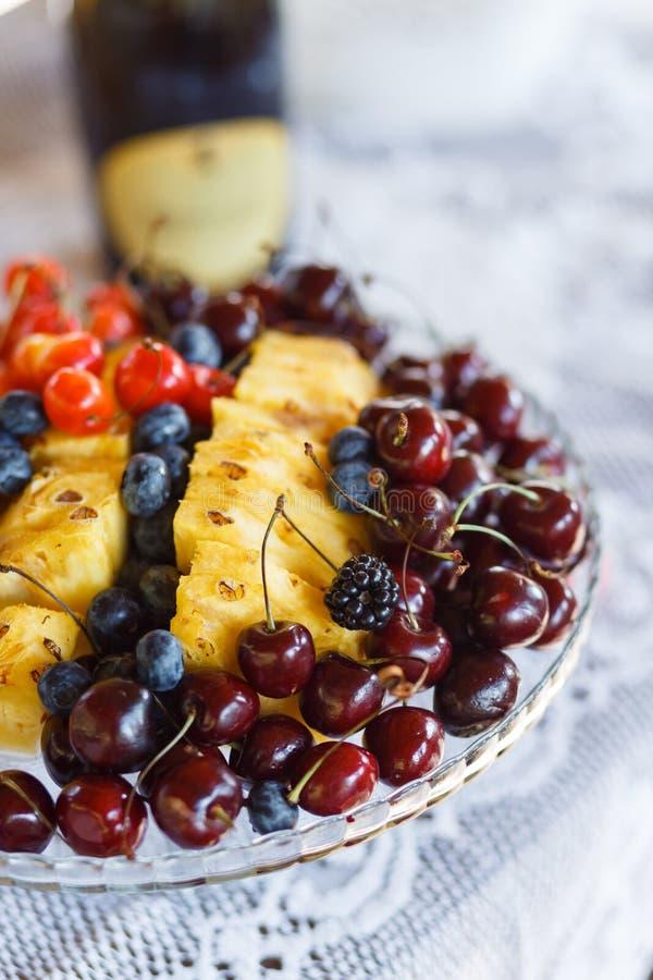 Las bayas y las frutas jugosas mienten en una placa imagen de archivo libre de regalías