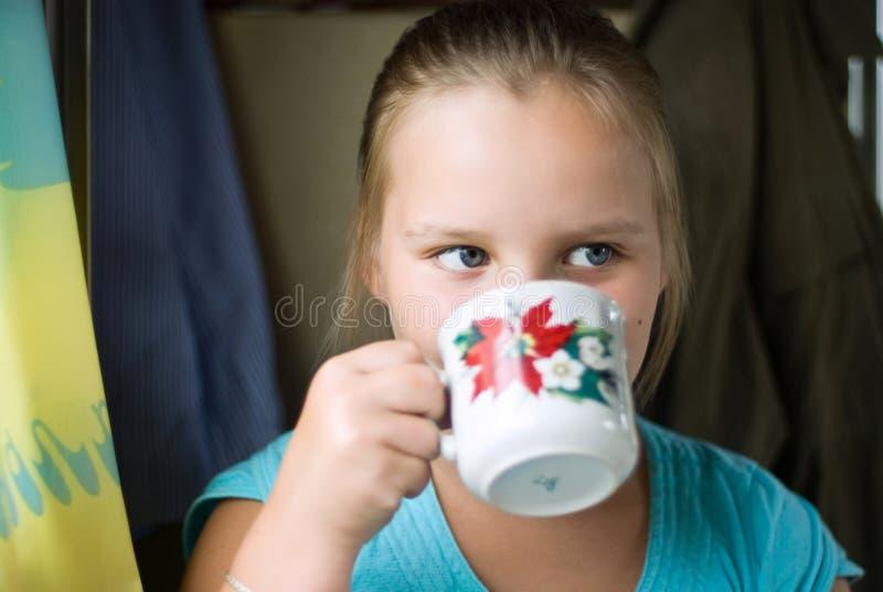 Las bebidas de la muchacha de una taza imagenes de archivo