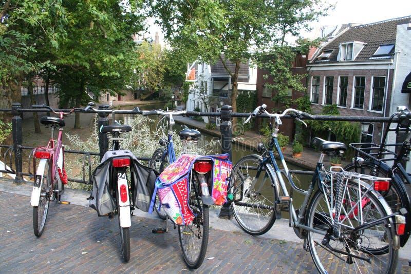las bicicletas parquearon en un brigde sobre un canal foto de archivo