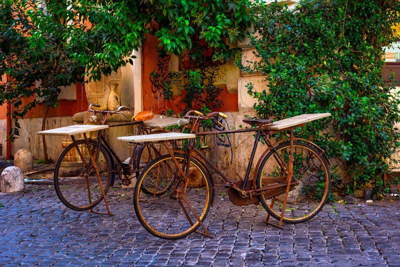 Las bicicletas son tabla de barra en inTrastevere acogedor de la calle en Roma imágenes de archivo libres de regalías