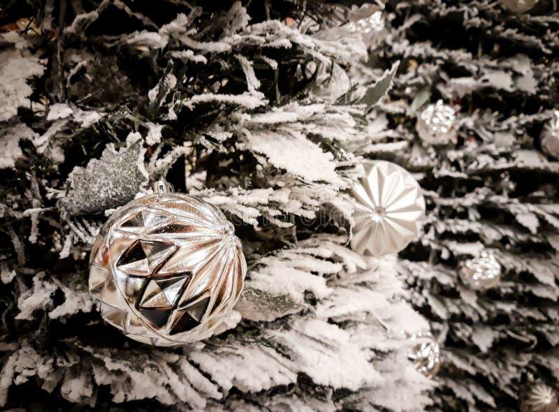 Las bolas blancas cuelgan en el árbol de navidad nevado fotografía de archivo