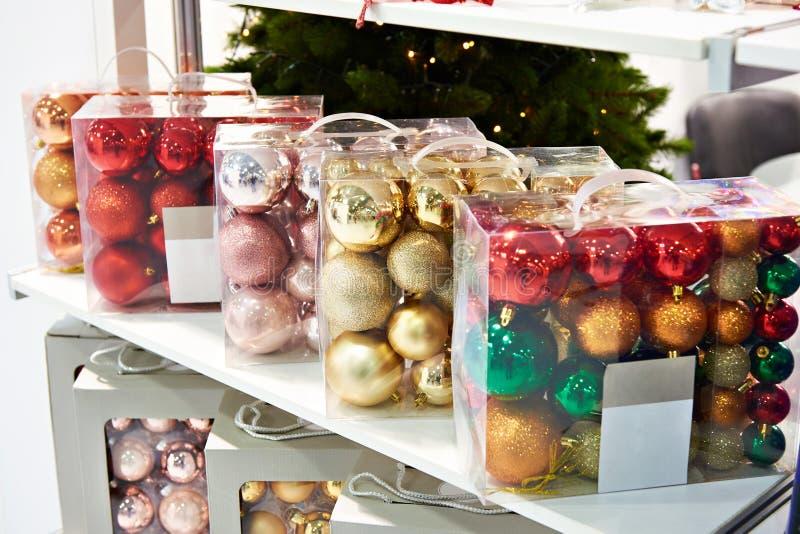 Las bolas coloreadas juegan para el árbol de navidad en tienda foto de archivo