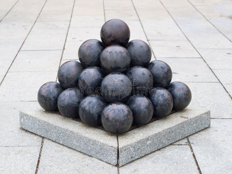 Las bolas de cañón negras viejas del hierro arreglaron en forma de la pirámide imágenes de archivo libres de regalías