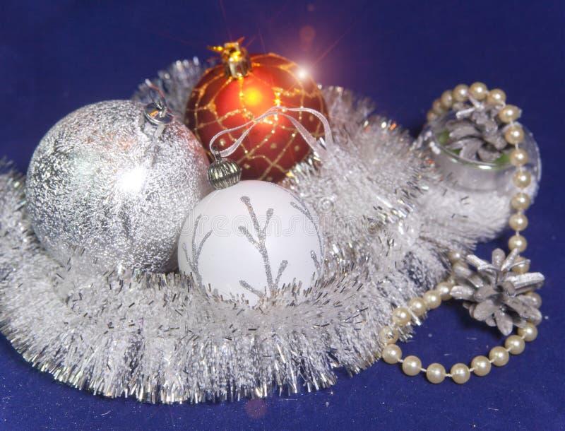 Las bolas de cristal blancas, rojas y de plata del ` s del Año Nuevo, la malla brillante, los conos y una perla gotea en un fondo imagen de archivo