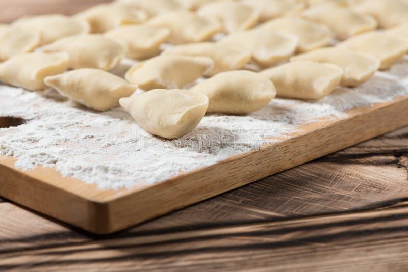 Las bolas de masa hervida crudas en tabla de cortar de madera, están listas para hervir También conocido como Vareniks Cocina tra imagenes de archivo