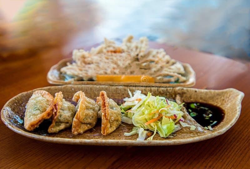 Las bolas de masa hervida fritas chinas en una placa con la salsa de soja y el marco vegetal del cierre de la ensalada tiran inte foto de archivo libre de regalías