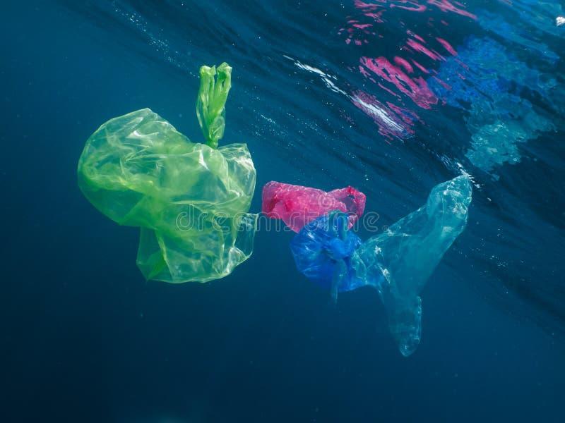 Las bolsas de plástico coloridas que flotan en el océano fotos de archivo