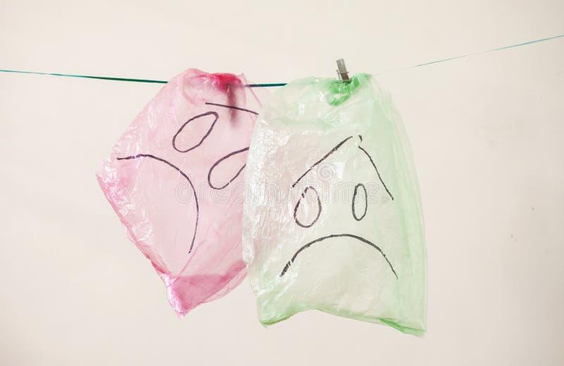 Las bolsas de plástico con emociones tristes contra el fondo blanco Concepto de la ecolog?a fotos de archivo