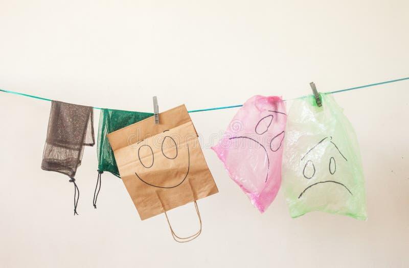 Las bolsas de plástico con emociones tristes y bolsos del papel y del eco con la emoción feliz contra el fondo blanco Concepto de foto de archivo libre de regalías