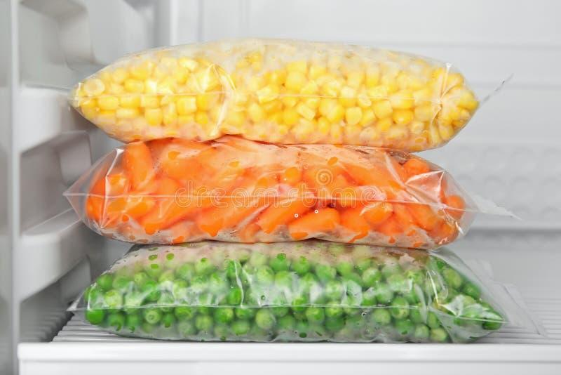 Las bolsas de plástico con las verduras congeladas en refrigerador fotografía de archivo