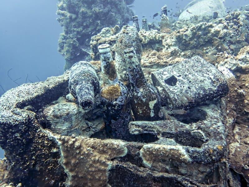 Las botellas cortezudas coralinas del motivo se sientan en naufragio subacuático fotos de archivo libres de regalías