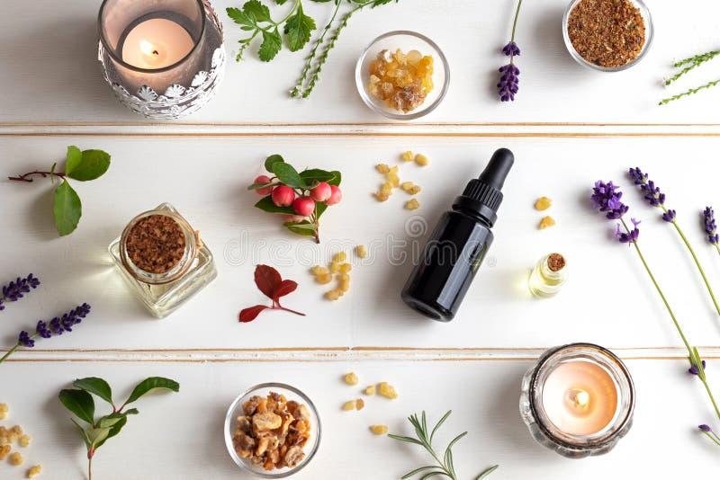 Las botellas de aceite esencial con incienso, wintergreen, lavende imagen de archivo