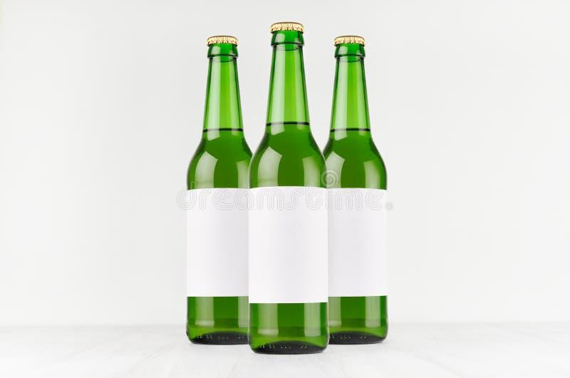 Las botellas de cerveza verdes del longneck 500ml con la etiqueta blanca en blanco en el tablero de madera blanco, imitan para ar imagen de archivo