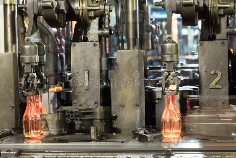 Las botellas de cristal calientes en el transportador son hechas por el manu de cristal fotografía de archivo