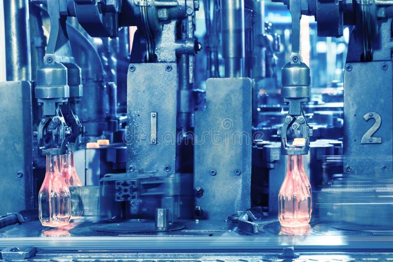 Las botellas de cristal calientes en transportador son hechas por el manufact de cristal imagenes de archivo