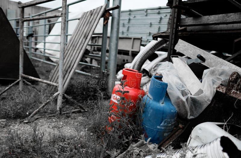Las botellas de gas comprimido vistas descargaron en una yarda de los constructores, mostrando las diversos herramientas de la co fotografía de archivo libre de regalías