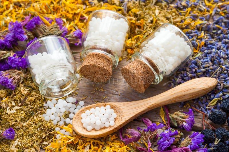 Las botellas de glóbulos de la homeopatía y secan las hierbas sanas fotos de archivo