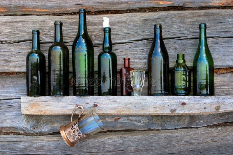 Las botellas, la copa y el vidrio se colocan en un estante imagen de archivo
