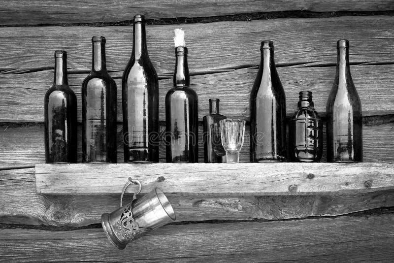 Las botellas, la copa y el vidrio se colocan en un estante imagen de archivo libre de regalías