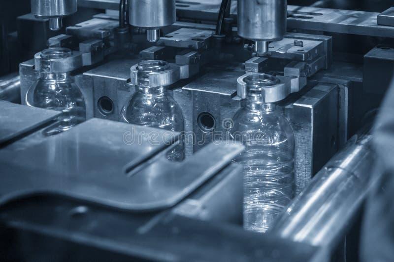 Las botellas PET de la máquina automática de tratamiento del molde soplado en la escena azul claro foto de archivo libre de regalías