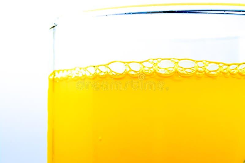 Las burbujas de la soda anaranjada en una macro de cristal del primer texturizaron backgro foto de archivo