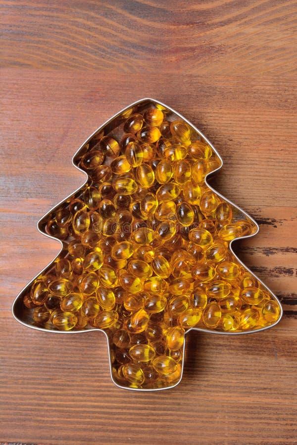 Las cápsulas con el aceite de pescado se separaron hacia fuera bajo la forma de árbol en un fondo de madera imágenes de archivo libres de regalías