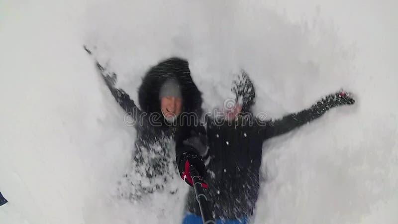 Las caídas del individuo y de la muchacha en la nieve acumulada por la ventisca Selfie con el monopod metrajes