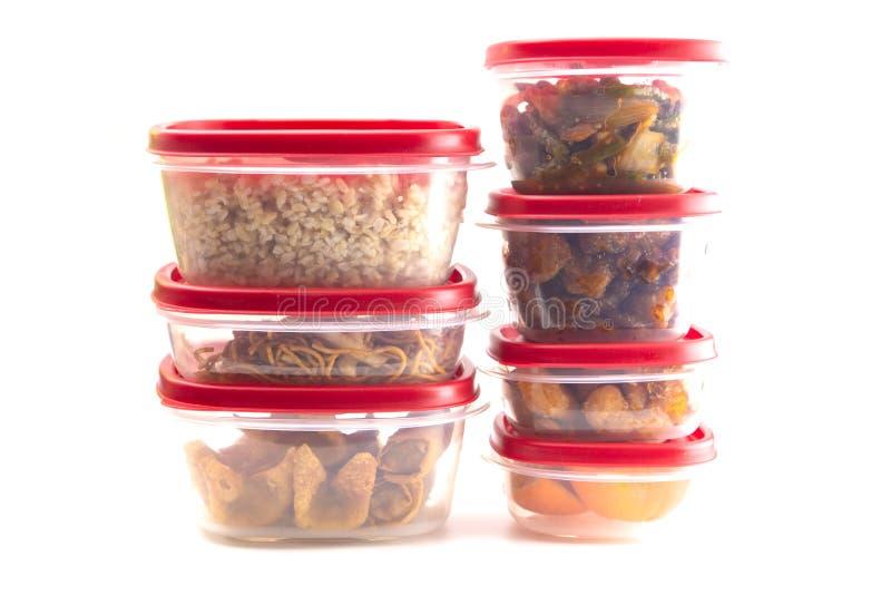 Las cajas con las tapas rojas llenaron de la comida de sobra imagenes de archivo