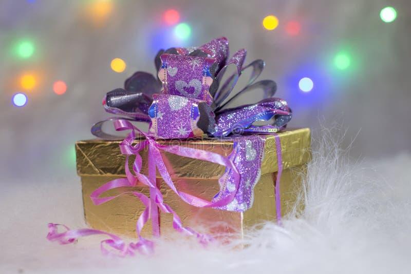 Las cajas de regalo con un arco rojo grande contra un bokeh del fondo del centelleo van de fiesta luces fotografía de archivo