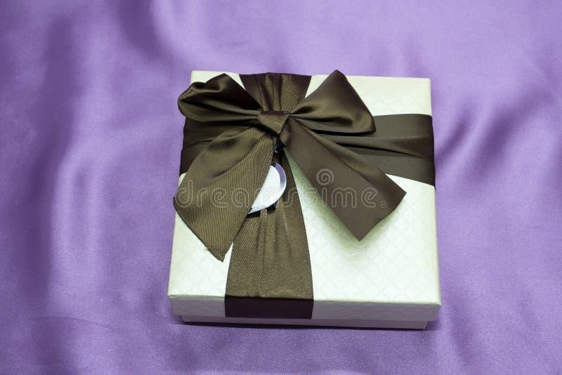 Las cajas de regalo con un arco rojo grande contra un bokeh del fondo del centelleo van de fiesta luces Regalo de lujo del Año Nu fotos de archivo libres de regalías