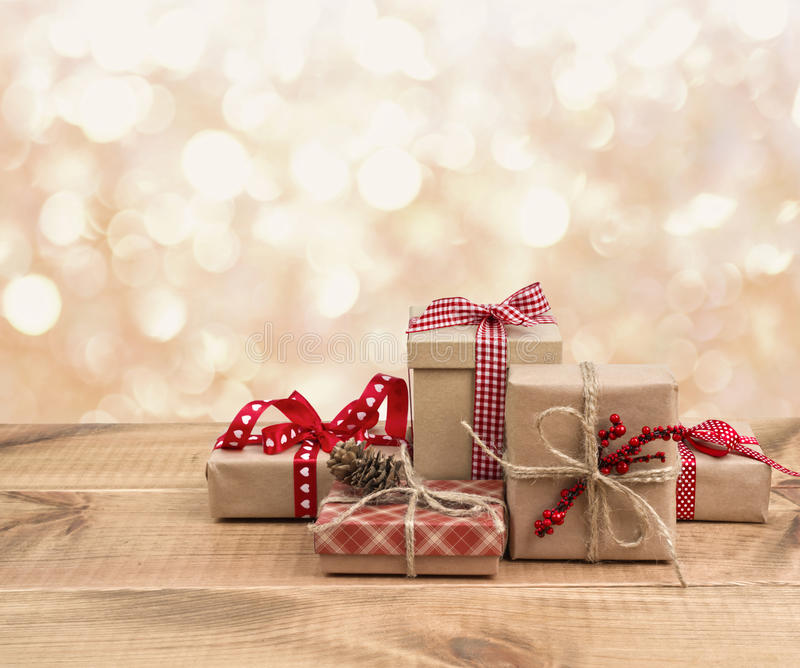 Las cajas de regalo de la Navidad en la tabla de madera sobre extracto encienden el fondo fotos de archivo libres de regalías