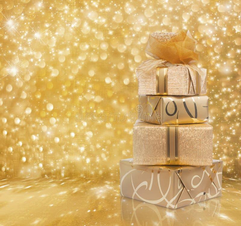 Las cajas de regalo hermosas en papel del oro con una seda subieron foto de archivo