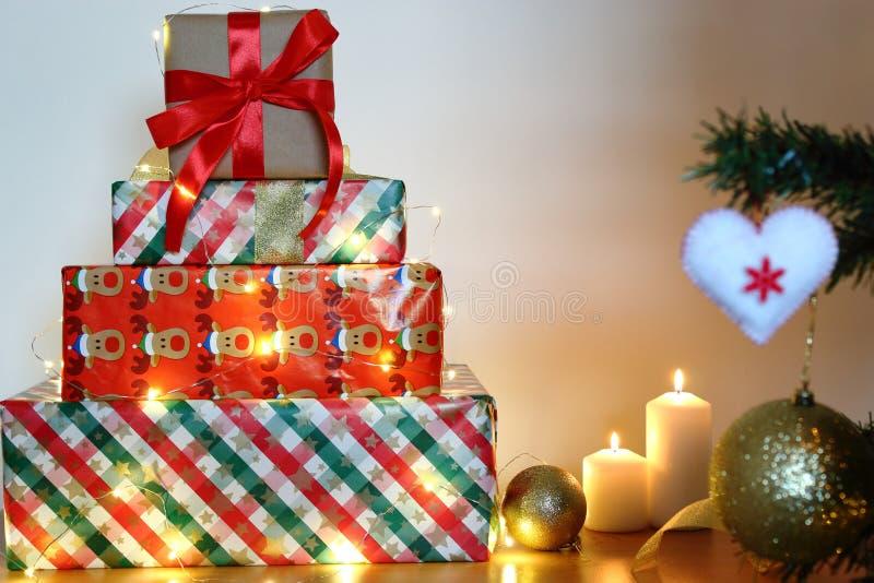 Las cajas de regalo de la Navidad con las velas y las bolas de oro arquean aislado en el fondo blanco imagenes de archivo
