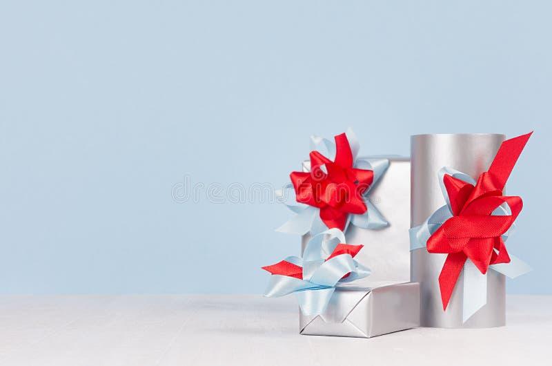 Las cajas de regalo de plata festivas de la elegancia con las cintas rojas y azules, arquean el primer en la tabla de madera blan fotos de archivo