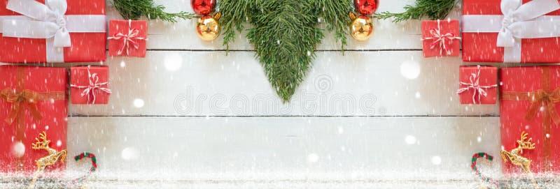 Las cajas de regalo rojas de la Navidad con los ornamentos verdes del pino y del adornamiento en el fondo de madera blanco del pa fotografía de archivo