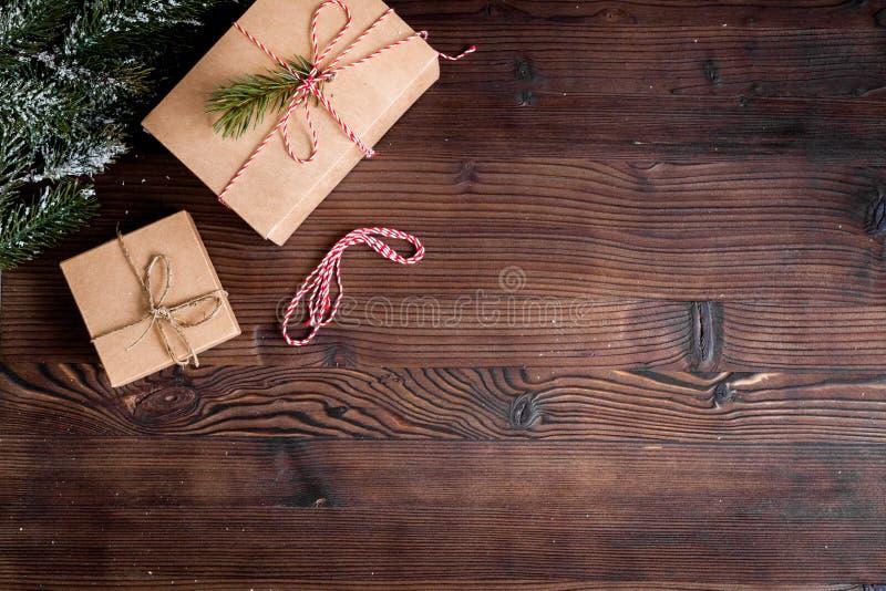 Las cajas de regalos con el abeto ramifican en la opinión superior del fondo de madera fotografía de archivo libre de regalías