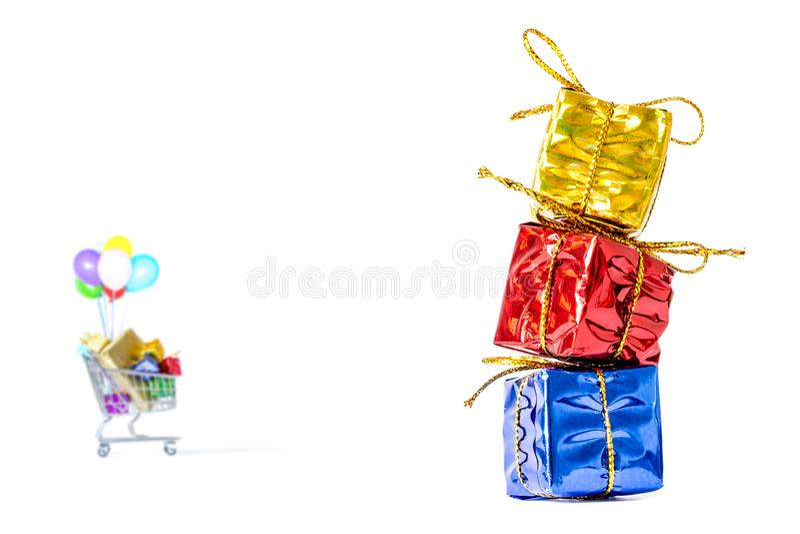 Las cajas de regalos en un paquete multicolor con un arco golded se colocan en un primer de la columna contra la perspectiva de u imagen de archivo libre de regalías