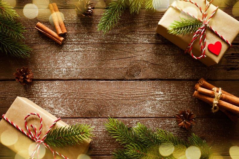 Las cajas de regalos de la Navidad con el abeto ramifican en la opinión superior del fondo de madera foto de archivo