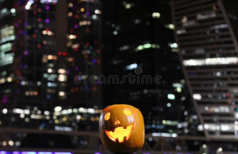 Las calabazas de Halloween dirigen Calabaza anaranjada con una sonrisa y ojos en ciudad de la noche y fondo de las luces foto de archivo