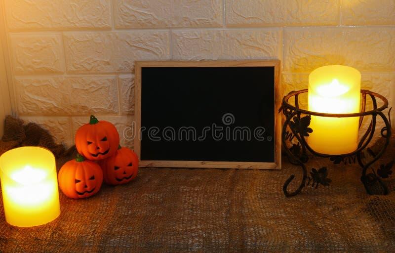 Las calabazas y las velas de la decoración de Halloween con la copia espacian al tablero negro en fondo de la pared imagenes de archivo