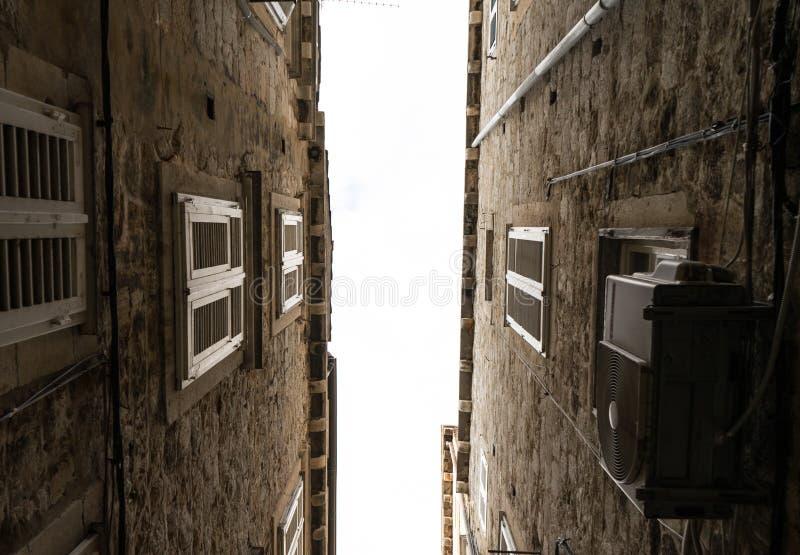 Las calles estrechas de la ciudad vieja de Dubrovnik en Croacia, la vista inferior del cielo entre las paredes de piedra de casas imagen de archivo libre de regalías
