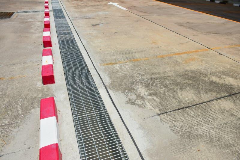 Las calles llueven los canales cerca del aparcamiento, tubos del canal fotografía de archivo